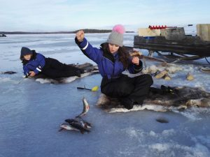 woman sits on ice fishing through a hole
