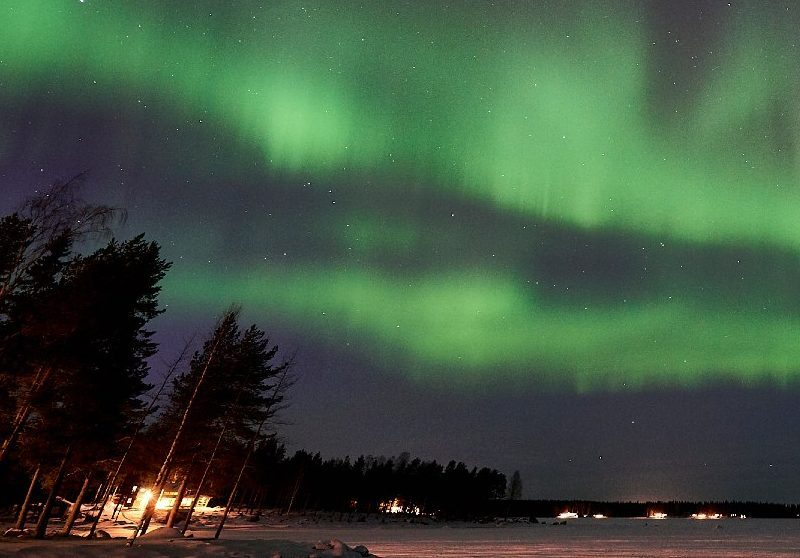northern lights over a cabin at the edge of the water