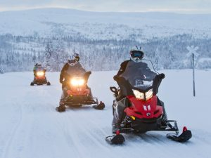 snowmobiles drive through the snowy frontier