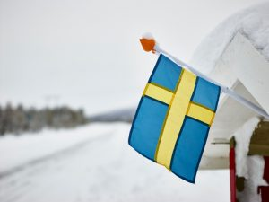 a swedish flag waves hangs off of the roof of a snowy house