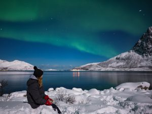 woman sits and watched northern lights over the water