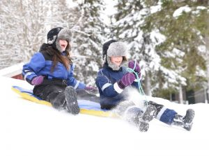 two children lay in the snow on a sledge
