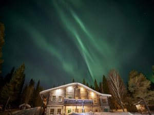 northern lights over a cabin hotel