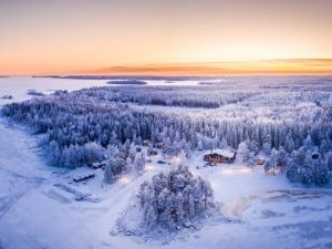 a panaromic shot of the snowy woodland landscape and a lodge in the middle