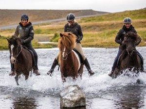 three people riding horses through a river