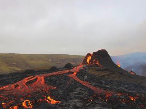 Volcano with lava flowing down it