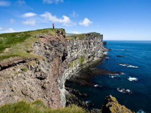 a cliff going into the sea with blue skies