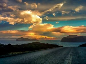road leading to ocean with sunset